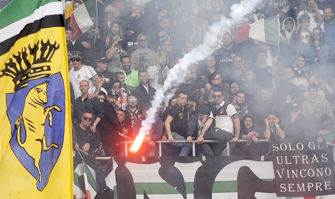 Juventus' supporters look on as a flare is thrown