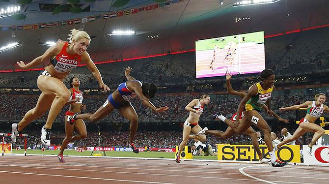 Jamaica's Danielle Williams (2nd from right) crosses the finish line ahead of Germany's Cindy Roleder (left) at the women's 100 metres hurdles final during the 15th IAAF World Championships at the National Stadium in Beijing, on Friday