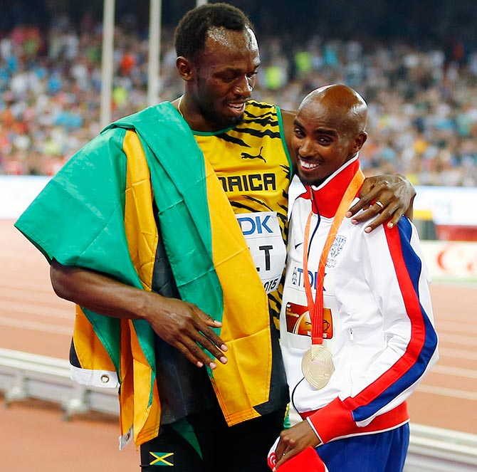 Usain Bolt of Jamaica (left) hugs Mo Farah of Britain, gold medal, after the podium ceremony for the men's 5,000 metres event during the during the 15th IAAF World Championships in Beijing