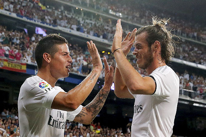Real Madrid's James Rodriguez (left) celebrates with teammate Gareth Bale after his goal against Real Betis during their La Liga match at Santiago Bernabeu stadium in Madrid on Saturday