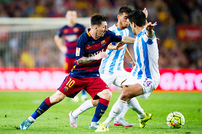 FC Barcelona's Lionel Messi tries to break the defensive barrier made by Malaga's Jose Luis Garcia 'Recio'