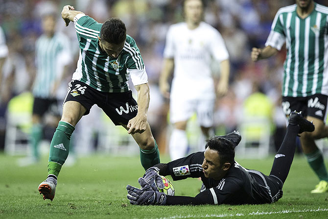 Real Madrid's goalkeeper Keylor Navas (right) stops the attack of Real Betis' Ruben Castro (left)