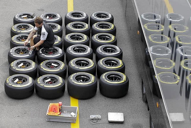 Mercedes mechanic checks the pressure of Pirelli tyres ahead of the Italian F1 Grand Prix in Monza