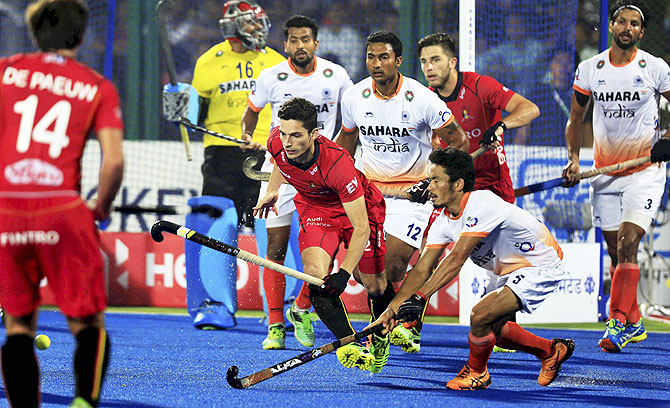 Players of India and Belgium (in red jersey) in action during the second semi-final of the Hockey World League in Raipur on Saturday