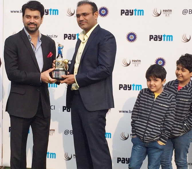Former India opener Virender Sehwag is felicitated by BCCI secretary Anurag Thakur (left), as the former's sons, Aryavir and Vedant look on during the ceremony at the Feroz Shah Kotla in New Delhi on Thursday