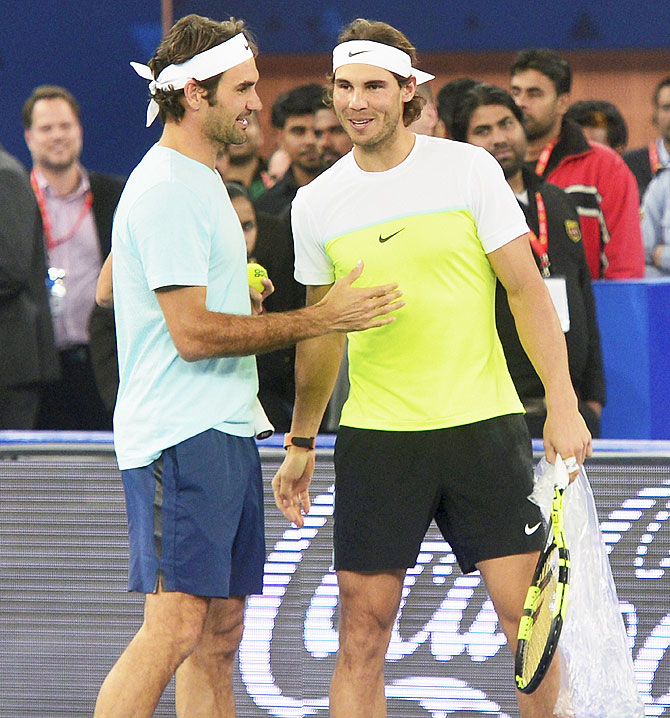 Rafael Nadal and Roger Federer hug at the net, after Nadal won their men's singles semi-final match at the Australian Open 2014 tennis tournament