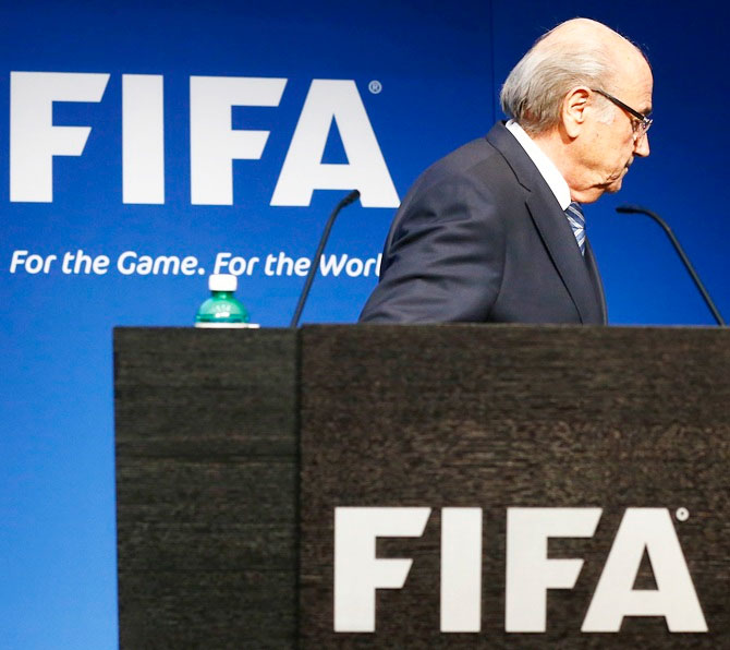 Sepp Blatter leaves after his statement during a news conference