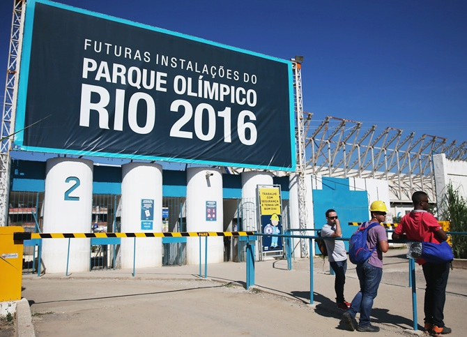 Workers stand at an entrance to the Olympic Park construction