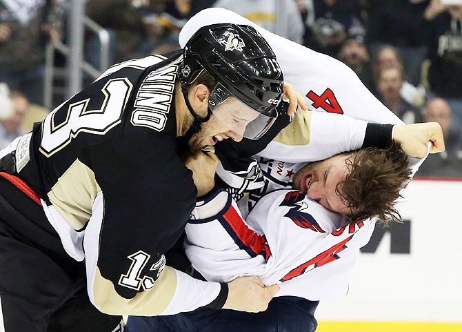 Washington Capitals defenseman Taylor Chorney (4) and Pittsburgh Penguins center Nick Bonino (13) fight during the second period of their ice hockey match at the CONSOL Energy Center in Pittsburgh on Monday