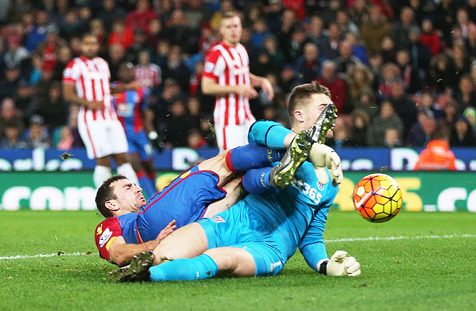 Crystal Palace's James McArthur and Stoke's Jack Butland are caught in a tangle as they vie for possession during their English Premier League match at Britannia Stadium on Saturday