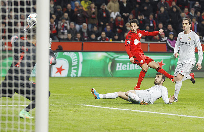 Bayer Leverkusen's Hakan Calhanoglu (centre) scores a goal past Atletico Madrid's goalkeeper Miguel Angel Moya (left) during their Champions League round of 16, first leg match in Leverkusen on Wednesday