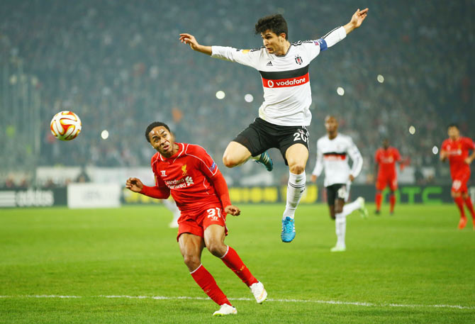Necip Uysal of Besiktas outjumps Raheem Sterling of Liverpool