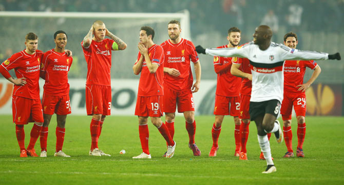 Liverpool players look dejected as Demba Ba of Besiktas (9) celebrates after Dejan Lovren of Liverpool misses the decisive kick in the penalty shootout