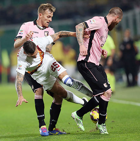 Palermo's Luca Rigoni (left) and Michael Morganella compete for the ball with Roma's Jose Hobales during their Serie A match at Stadio Renzo Barbera in Palermo on Saturday