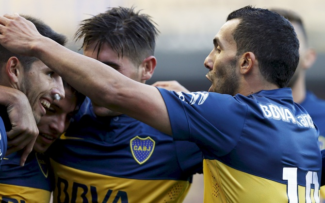 Boca Juniors' Carlos Tevez, right, embraces teammates