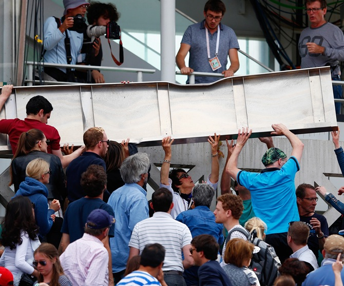 Spectators help lift a piece of the roof from Court Philippe Chatrier