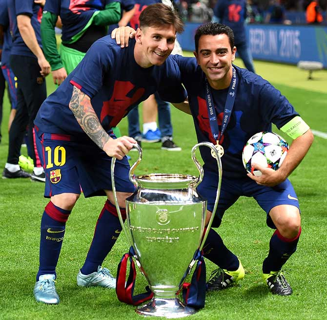 FC Barcelona's Lionel Messi and Xavi Hernandez celebrate with the trophy after winning the UEFA Champions League final against Juventus at Olympic Stadium in Berlin on June 6