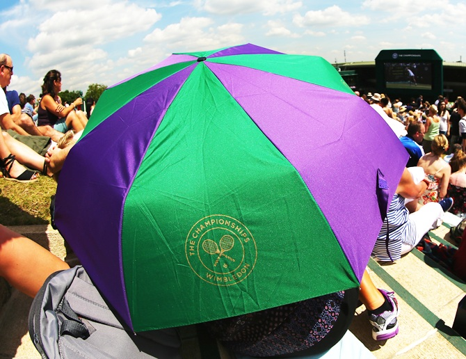 Fans sitting on Murray mound shelter from the sun