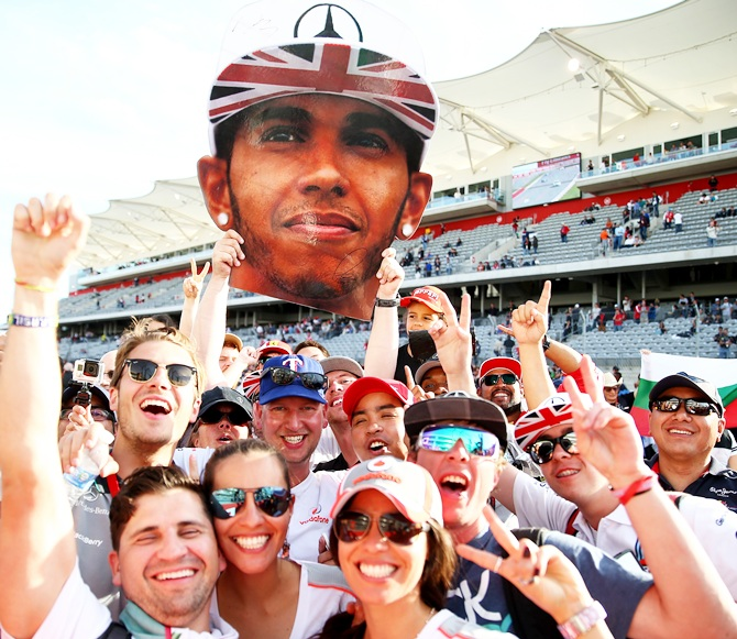 Fans of Lewis Hamilton of Great Britain and Mercedes GP celebrate his victory