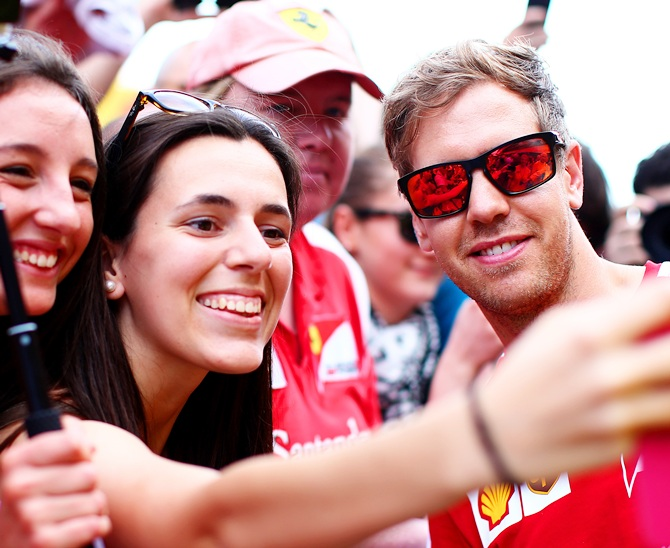 Sebastian Vettel of Germany and Ferrari poses for a photograph with fans