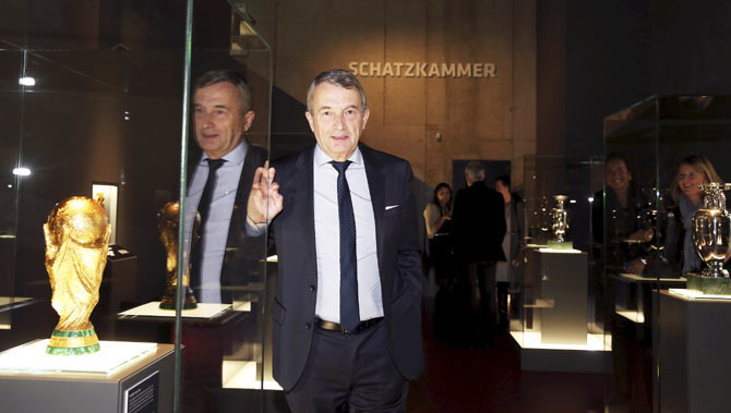Wolfgang Niersbach, president of the German Football Association (DFB), stands next to the trophy of the Brazil 2014 World Cup in the treasure room during the opening of the new German soccer museum in Dortmund