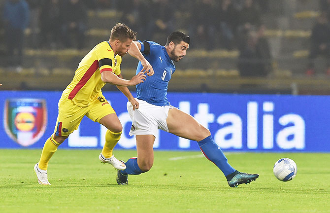 Italy's Graziano Pelle (left) is challenged by a Romania player during their international friendly at Stadio Renato Dall'Ara in Bologna on Tuesday