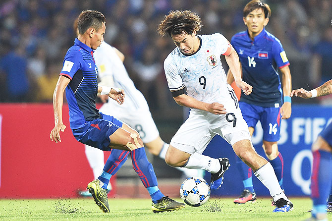 Japan's Shinji Okazaki (right) competes for the ball against his Cambodian opponent during their 2018 FIFA World Cup Qualifier in Phnom Penh, Cambodia, on Tuesday