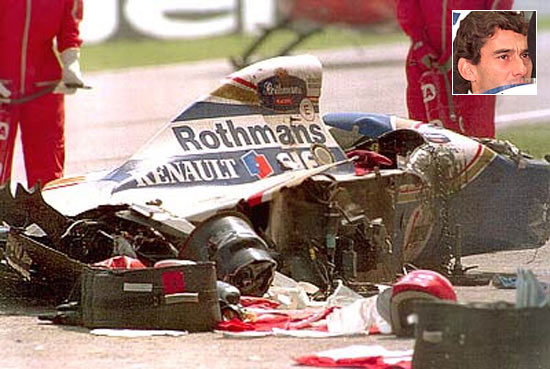 The Rothmans Williams car of Senna lies shattered on the track after he crashed into the concrete barrier
