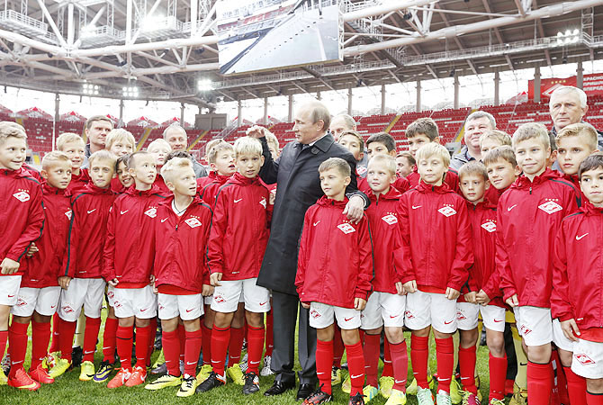 Russian President Vladimir Putin talks to young soccer players during a visit to Spartak's stadium Otkrytie Arena in Moscow