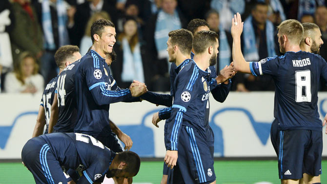 Real Madrid's Cristiano Ronaldo (left) celebrates with teammates after scoring the opening goal against Malmo FF during their Champions League group A match at Malmo New Stadium in Malmo, Sweden on Wednesday