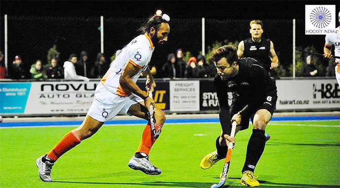 India captain Sardar Singh is blocked by a Kiwi defender