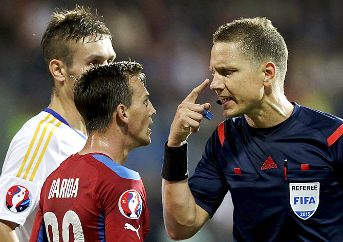 Referee Martin Strombergsson (right) speaks with Czech Republic's Vladimir Darida (centre) and Kazakhstan's Baurzhan Dzholchiyev during their match in Plzen, Czech Republic