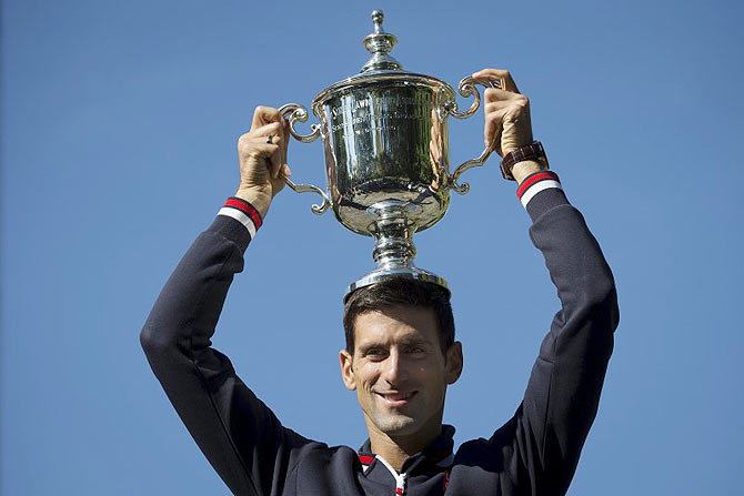 Novak Djokovic of Serbia poses with the champion's trophy in Central Park in New York, a day after winning the US Open Championships men's tennis tournament