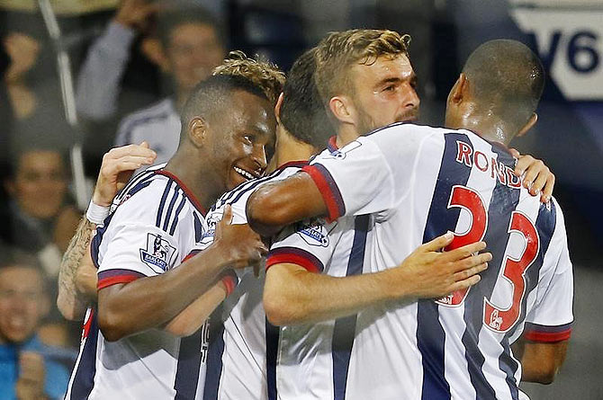 Saido Berahino celebrates with teammates after scoring the first goal for West Brom