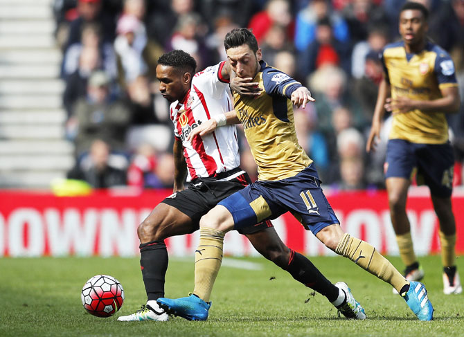 Arsenal's Mesut Ozil is challenged by Sunderland's Jermain Defoe during their English Premier League match at the Stadium of Light on Sunday