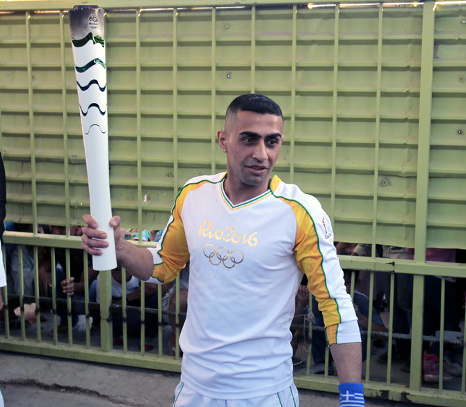 Rediff Sports - Cricket, Indian hockey, Tennis, Football, Chess, Golf - PHOTOS: Syrian amputee carries Rio Olympic flame through Athens refugee camp