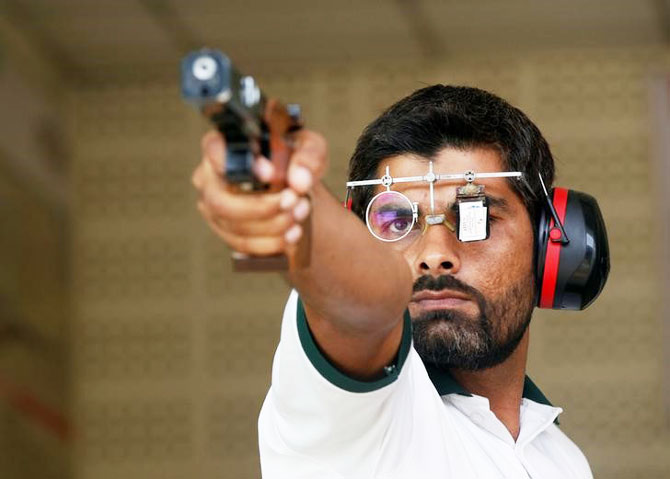 Ghulam Mustafa Bashir aims his pistol during a practice session at the Pakistan Navy Shooting Range in Karachi