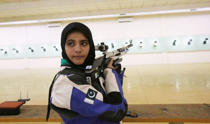 Minhal Sohail looks back as she prepares to shoot her air rifle during a practice session at the Pakistan Navy Shooting Range in Karachi on July 29, 2016