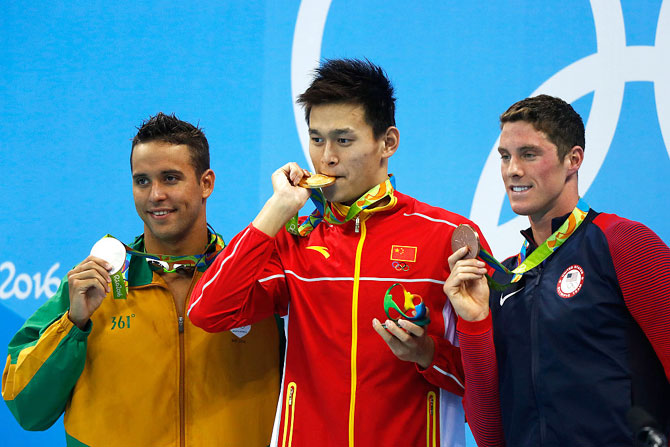 Silver medalist Chad le Clos of South Africa, gold medalist Yang Sun of China and bronze medalist Conor Dwyer of the United States pose on the podium during the medal ceremony for the Men's 200m Freestyle Final on Day 3 of the Rio 2016 Olympic Games at the Olympic Aquatics Stadium in Rio de Janeiro, Brazil, on Monday