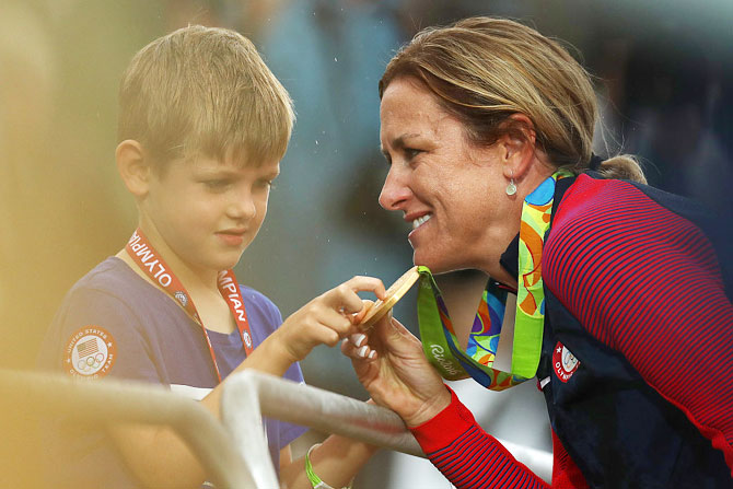Gold medalist Kristin Armstrong of the United States shows her medal to her son Lucas William Savola after the medal ceremony for the Cycling Road Women's Individual Time Trial on Day 5 of the Rio 2016 Olympic Games at Pontal in Rio de Janeiro