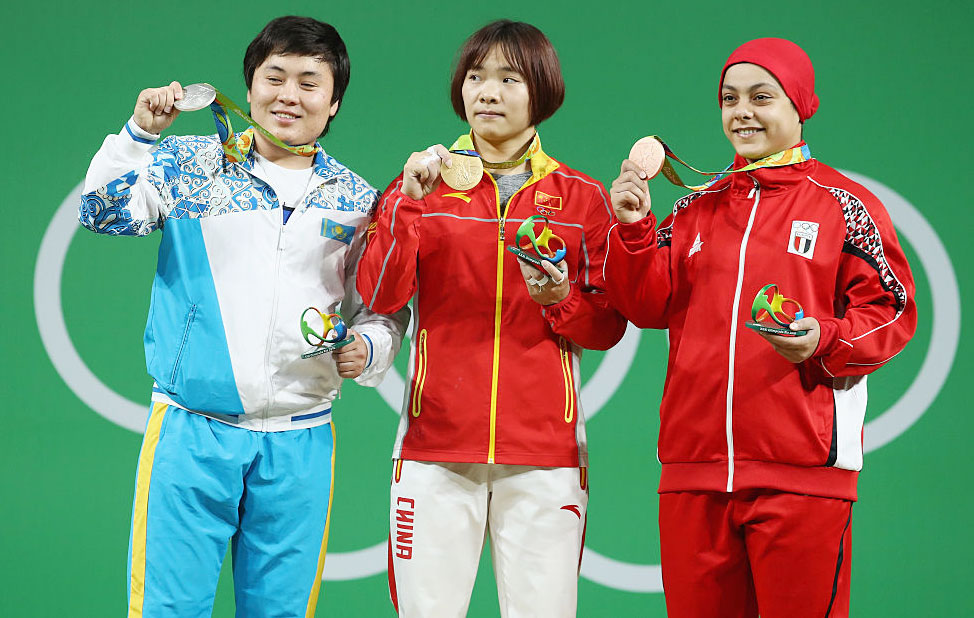 Gold medalist, Yanmei Xiang of China (centre), silver medalist Zhazira Zhapparkul of Kazakhstan and bronze medalist Sara Ahmed of Egypt pose on the podium after the Women's 69kg Group A weightlifting contest on Wednesday