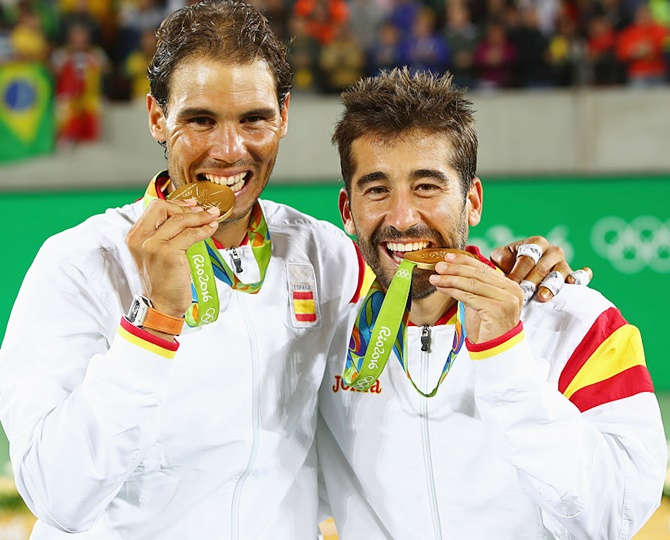 Gold medalists Rafael Nadal and Marc Lopez of Spain celebrate with their medals after the men's doubles gold medal match on August 13