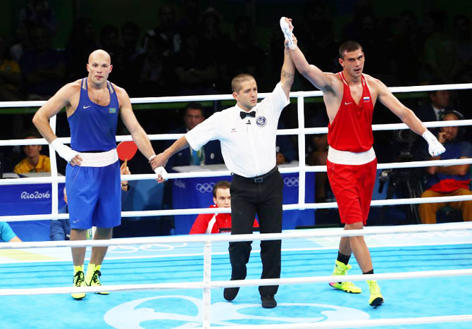 Evgeny Tishchenko of Russia reacts after winning his bout against Vassiliy Levit of Kazakhstan to win the Men's Heavy (91kg) gold medal on Monday