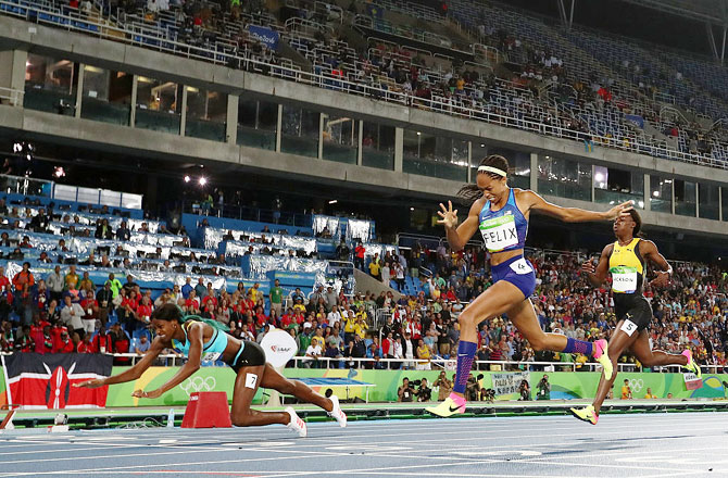 Shaunae Miller of the Bahamas (left) dives over the finish line ahead of silver medalist Allyson Felix of the United States (centre) and bronze medalist Shericka Jackson of Jamaica (right) to win the gold medal in the Women's 400m Final at the Rio 2016 Olympic Games at the Olympic Stadium on Monday
