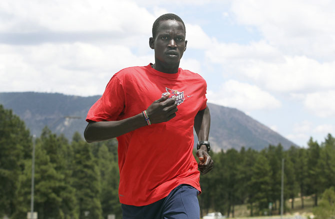 Guor Marial runs along a street in Flagstaff, Arizona during a training session in 2012