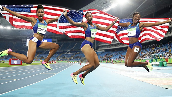 From left, bronze medalist Kristi Castlin, gold medalist Brianna Rollins and silver medalist Nia Ali of the United States celebrate with American flags after the women's 100m hurdles final on August 17