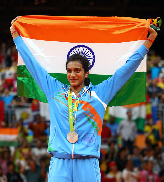 Silver medallist P V Sindhu of India celebrates during the medal ceremony after losing to Carolina Marin of Spain in the women's singles badminton final at the Rio Olympics