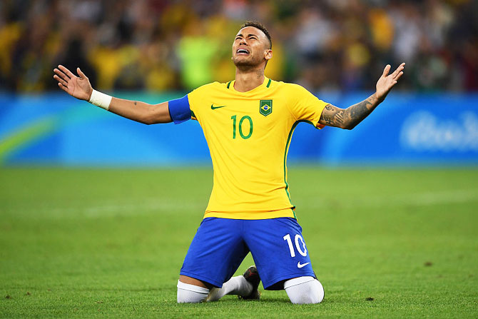 Neymar celebrates scoring the winning penalty to help Brazil win the men's football final against Germany at the Maracana Stadium at the Rio 2016 Olympic Games on August 20