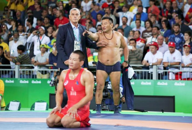 Mandakhnaran Ganzorig of Mongolia and his coach react after the match against Ikhtiyor Navruzov of Uzbekistan during the Men's Freestyle 65 kg Bronze medal wrestling match on August 21