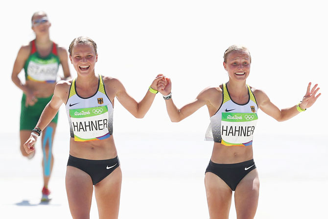 Anna Hahner (left) of Germany and her sister Lisa Hahner react as they approaches the finish line during the Women's Marathon of the Rio 2016 Olympic Games at the Sambodromo on August 14